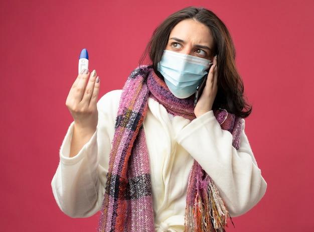 분홍색 벽에 고립 된 측면을보고 온도계를 들고 전화로 얘기하는 마스크와 가운과 스카프를 착용하는 젊은 아픈 여자를 찡그림