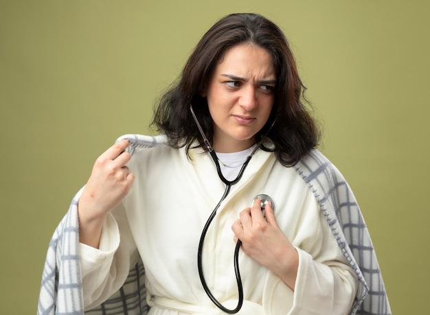 Accigliata giovane donna malata che indossa veste e stetoscopio avvolto in un plaid ascoltando il suo battito cardiaco afferrando il plaid guardando il lato isolato sul muro verde oliva