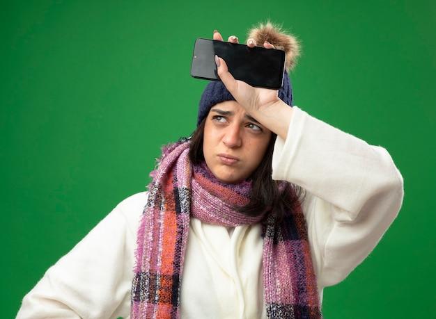 가운 겨울 모자와 스카프를 착용하는 찡그림 젊은 아픈 여자는 녹색 벽에 고립 된 측면을보고 이마를 만지고 휴대 전화를 들고
