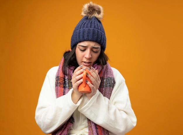Accigliata giovane donna malata che indossa un abito invernale cappello e sciarpa che tiene e guardando dentro la tazza di tè isolata sulla parete arancione