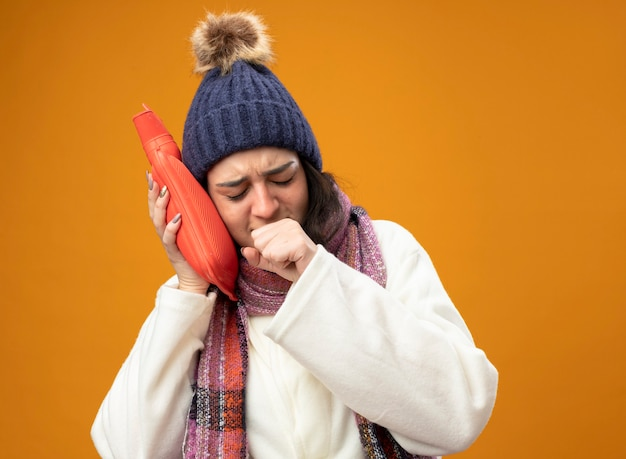 Accigliata giovane donna malata che indossa abito invernale cappello e sciarpa toccando la testa con la borsa dell'acqua calda tosse tenendo il pugno vicino alla bocca con gli occhi chiusi isolato sul muro arancione