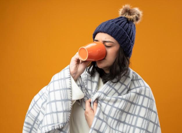 オレンジ色の壁に隔離された目を閉じて格子縞をつかむ格子縞の飲み物のカップに包まれたローブの冬の帽子をかぶった眉をひそめている若い病気の女性
