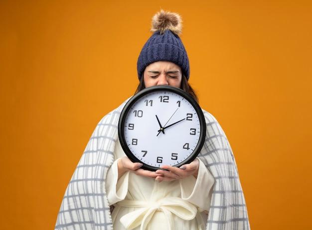 Нахмурившаяся молодая больная женщина в зимней шапке, завернутой в плед, держит часы с закрытыми глазами, изолированными на оранжевой стене