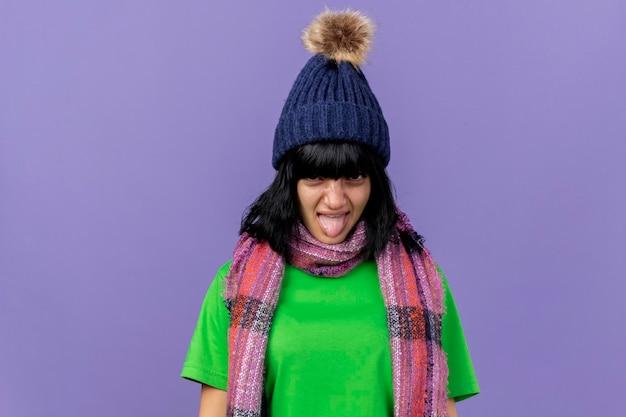 Accigliata giovane donna malata che indossa un cappello invernale e sciarpa guardando la parte anteriore che mostra la linguetta isolata sulla parete viola con lo spazio della copia