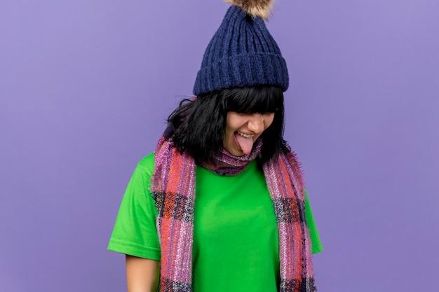 Accigliata giovane donna malata che indossa un cappello invernale e sciarpa girando testa a lato che mostra la linguetta isolata sulla parete viola con lo spazio della copia