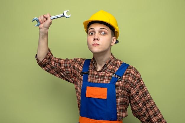 Accigliato giovane costruttore maschio che indossa l'uniforme che tiene in mano una chiave inglese