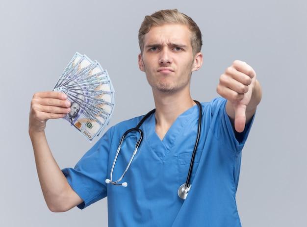 Accigliato giovane medico maschio che indossa l'uniforme del medico con lo stetoscopio che tiene contanti che mostra il pollice giù isolato sul muro bianco