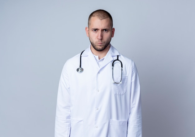 Frowning young male doctor wearing medical robe and stethoscope around his neck standing and looking isolated on white  with copy space