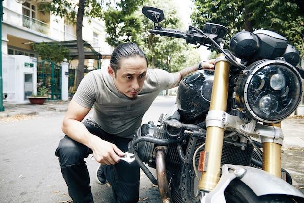 彼の古い壊れた自転車をチェックする手にレンチを持って若い男を溺れさせる