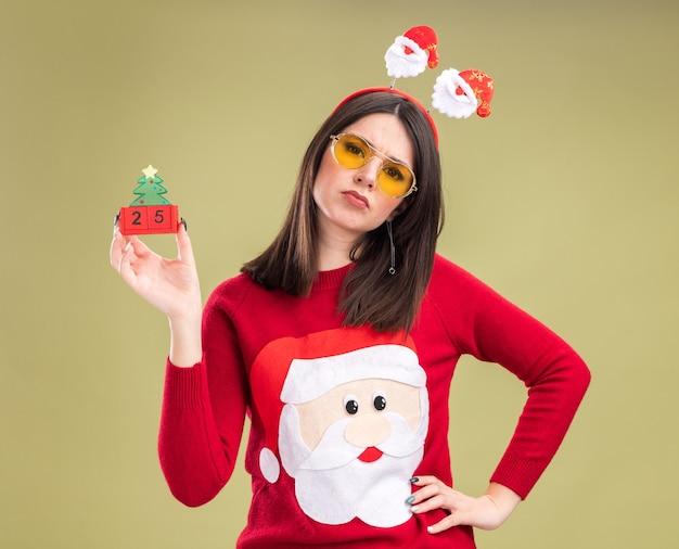 サンタクロースのセーターとヘッドバンドを身に着けている眉をひそめている若いかわいい白人の女の子は、日付を保持する手でクリスマスツリーのおもちゃを保持している眼鏡 無料写真