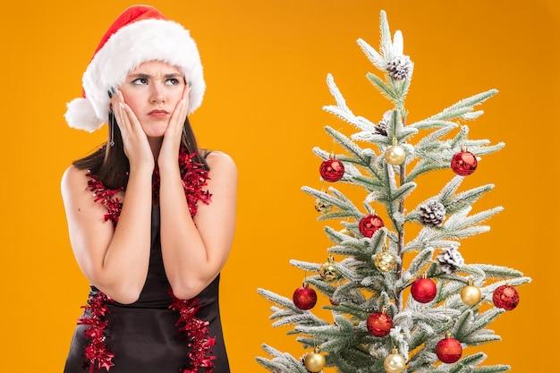 サンタの帽子と見掛け倒しのガーランドを首の周りに身に着けている眉をひそめている若いかわいい白人の女の子は、オレンジ色の背景で隔離された顔を見上げて手を保つ装飾されたクリスマスツリーの近くに立っています