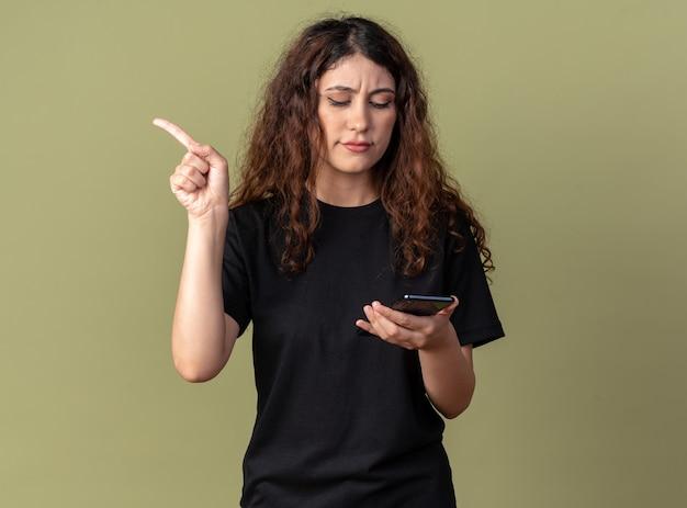 Нахмурившись, молодая красивая девушка держит и смотрит на мобильный телефон, указывая в сторону