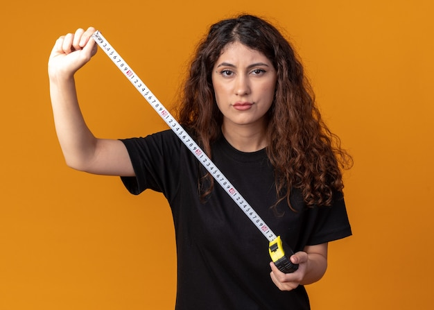 Frowning young pretty girl holding tape meter