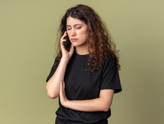 Frowning young pretty girl talking on phone looking down isolated on olive green wall with copy space