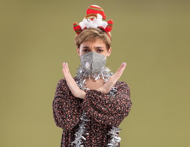サンタクロースのヘッドバンドと首の周りに見掛け倒しのガーランドを身に着けている眉をひそめている若いかわいい女の子は、オリーブグリーンの背景に分離されたジェスチャーをしないカメラを見て保護マスクと