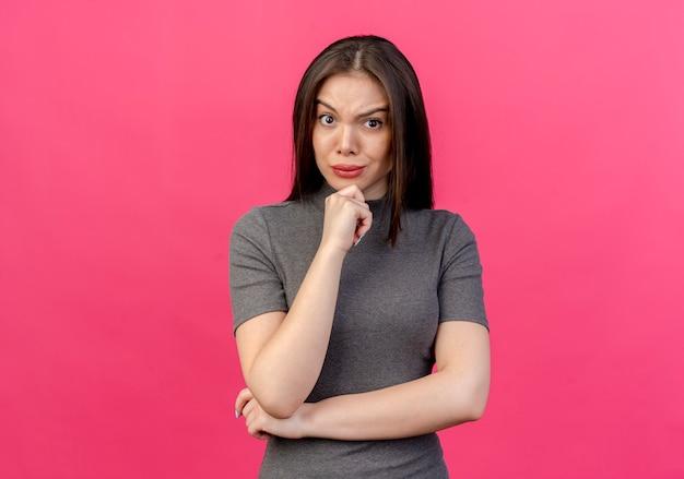Accigliata giovane donna graziosa che mette le mani sotto il gomito e sul mento isolato su sfondo rosa con spazio di copia