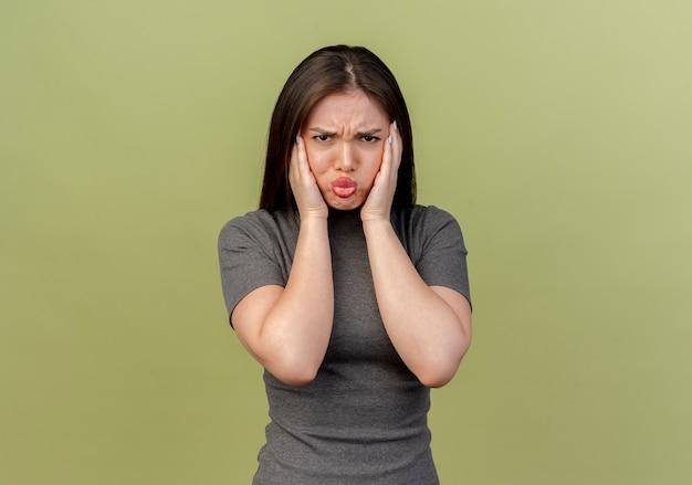 眉をひそめている若いきれいな女性がオリーブグリーンの壁にキスジェスチャーをしている顔に手を置く