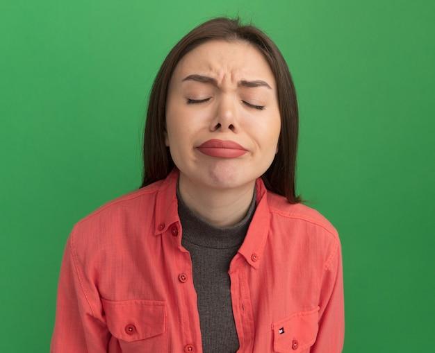 Accigliata giovane donna graziosa con gli occhi chiusi isolata sul muro verde