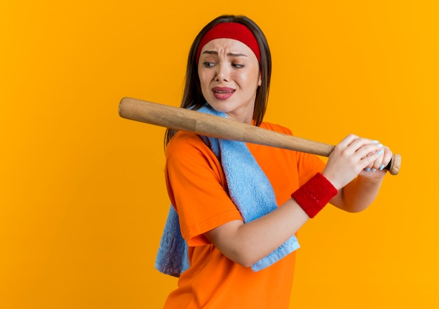 Frowning young sporty woman wearing headband and wristbands with towel on shoulder holding baseball bat looking at side isolated on orange wall with copy space