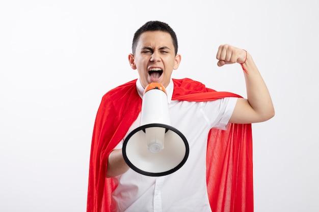 コピースペースと白い背景で隔離のラウドスピーカーで叫んでいるカメラを見て拳を上げて赤いマントで眉をひそめている若いスーパーヒーローの少年