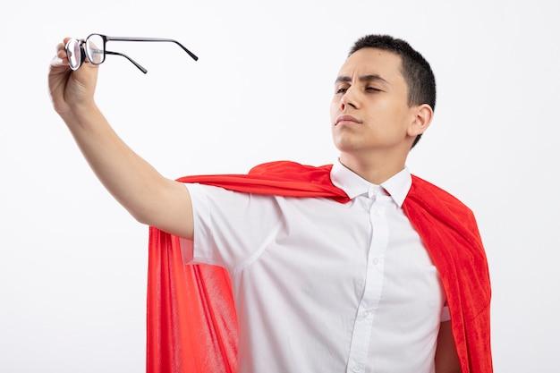 白い背景で隔離されたそれらを見て眼鏡を伸ばして赤いマントで眉をひそめている若いスーパーヒーローの少年
