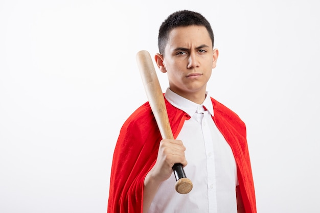 Frowning young superhero boy in red cape holding baseball bat on shoulder looking at camera isolated on white background with copy space