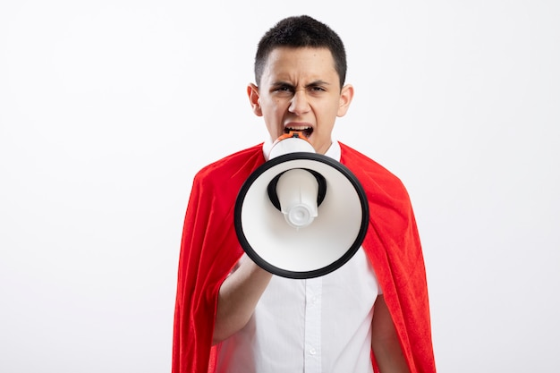 Frowning young superhero boy in red cape looking at camera talking by speaker isolated on white background with copy space