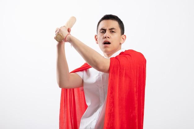 Accigliato giovane supereroe ragazzo in mantello rosso alzando la mazza da baseball in su guardando la fotocamera sempre pronto a colpire isolato su sfondo bianco con spazio di copia