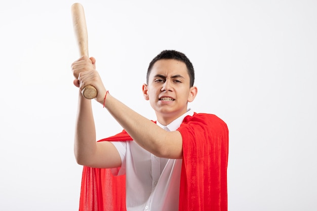 Frowning young superhero boy in red cape raising baseball bat up looking at camera getting ready to hit isolated on white background with copy space