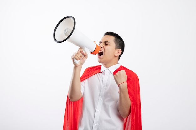 Frowning young superhero boy in red cape shouting in loud speaker with closed eyes clenching fist isolated on white background with copy space