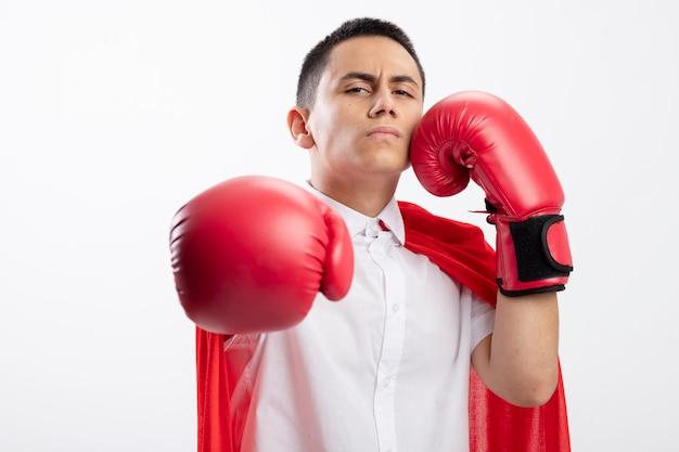 Accigliato giovane ragazzo supereroe in mantello rosso che indossa guanti di scatola guardando la telecamera allungando la mano verso la telecamera toccando il viso con un altro isolato su sfondo bianco con spazio di copia