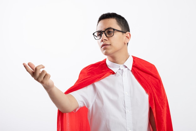 Frowning young superhero boy in red cape wearing glasses looking and pointing at side isolated on white background