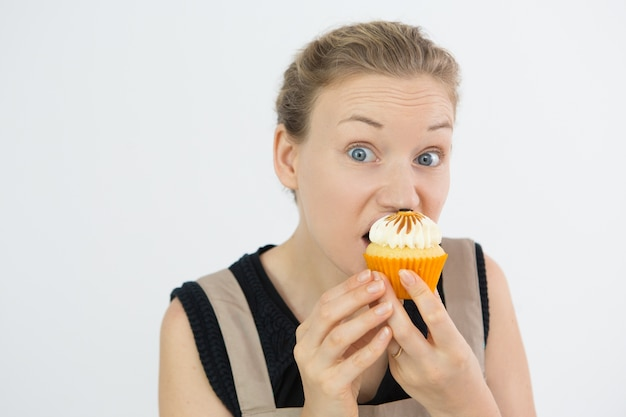 Frowning young woman eating cupcake with greed