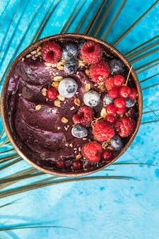 コンクリートの背景にラズベリー、バナナ、ブルーベリー、フルーツ、グラノーラを添えたココナッツシェルの冷凍アサイースムージー。朝食、夏の雰囲気のための健康的な食事、上面図、テキストのためのスペース