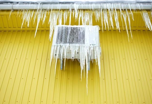 Замороженный кондиционер в ледяных сосульках на стене