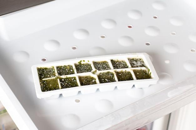 Замороженный базилик в кубиках льда в морозилке. замороженные овощи. концепция здорового питания.