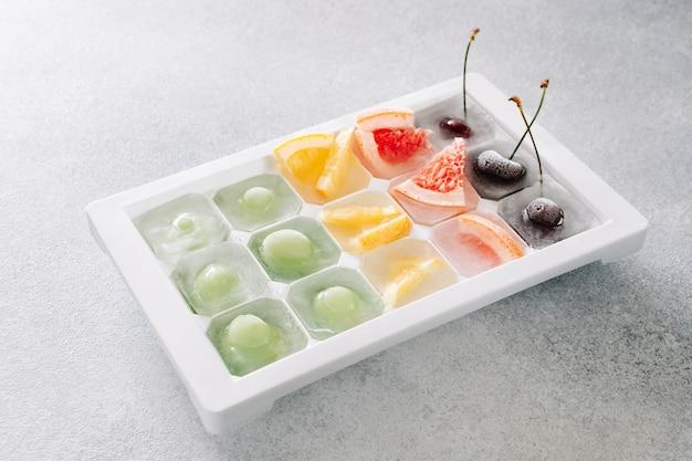 냉동 딸기와 과일은 밝은 배경에 얼음이 있는 쟁반에 놓여 있습니다