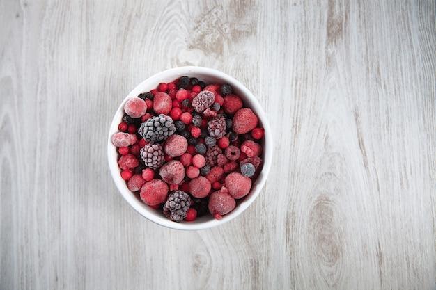 冷凍ベリー、ブラックカラント、レッドカラント、ラズベリー、ブルーベリー。孤立した素朴な木製のテーブルの上のヴィンテージセラミック白いボウルの上面図。