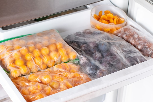 Замороженные ягоды в морозилке. замороженные сливы, алыча на полке морозильной камеры.