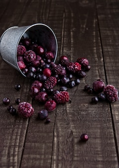 Замороженные ягоды смешать в черной миске на деревянном фоне