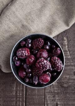 Frozen berries mix in small steel bucket on wooden table.