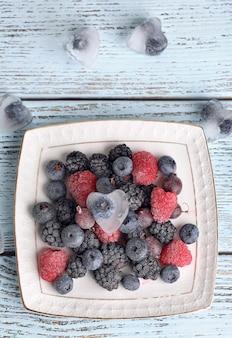 Замороженные ягоды на цветной деревянной поверхности