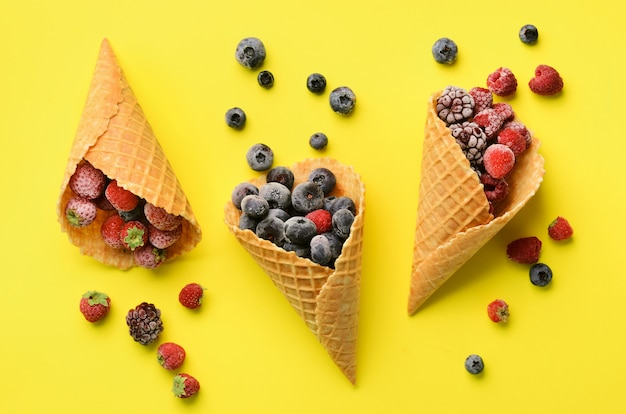 Frozen berries - strawberry, blueberry, blackberry, raspberry in waffle cones on yellow background.