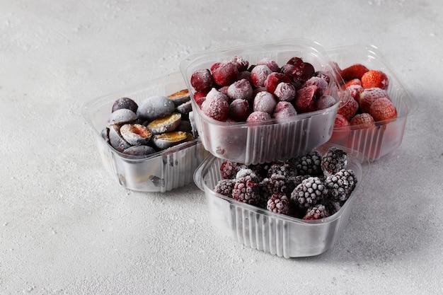 コンクリートの灰色の背景の収納ボックスにサクランボ、イチゴ、プラム、ブラックベリーなどの冷凍ベリー