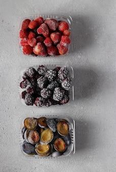 コンクリートの灰色の背景の収納ボックスにイチゴ、ブラックベリー、プラムなどの冷凍ベリー。上からの眺め