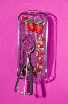 Шербет из замороженных ягод на ярко-фиолетовом полотне. вертикальное фото. монохромный