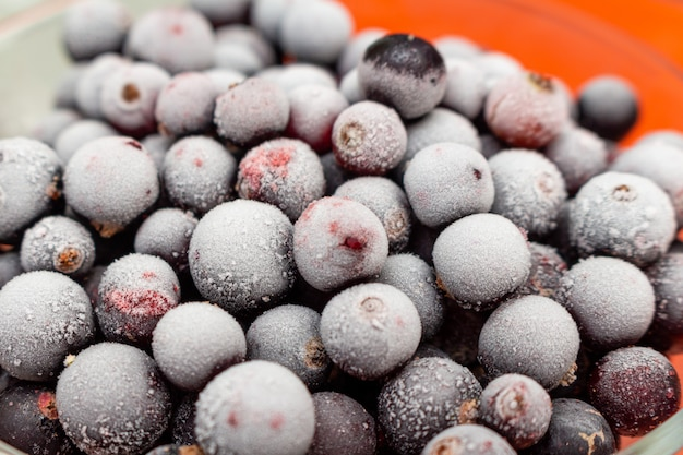 Frozen black currant berries in a glass jar close up
