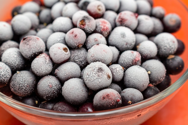 Frozen black currant berries in a glass jar