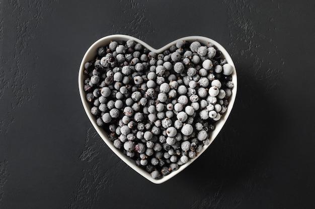 위에서 검은 배경 보기에 심장 모양의 접시에 냉동된 검은 건포도