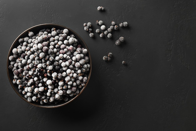 Frozen black currant in plate on a black background with copy space